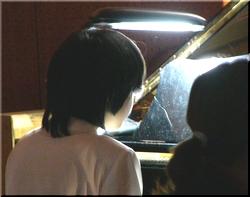 ピアノの伴奏をするひとみの後姿